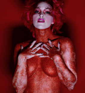 A woman looking like she's painted red, nude with her arms up across her breasts and hands with fingers spread near her throat. Her face is painted pure white and she has on a lot of makeup. Her hair is blonde, short and curly and the background is red.