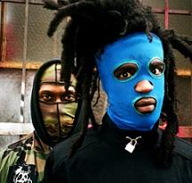 Two men one in front with dreds sticking up off his head and a bright blue mask and a guy behind him with a camouflage mask