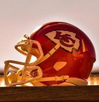 Red football helmet with a YC logo on the side sitting sideways on a wood table
