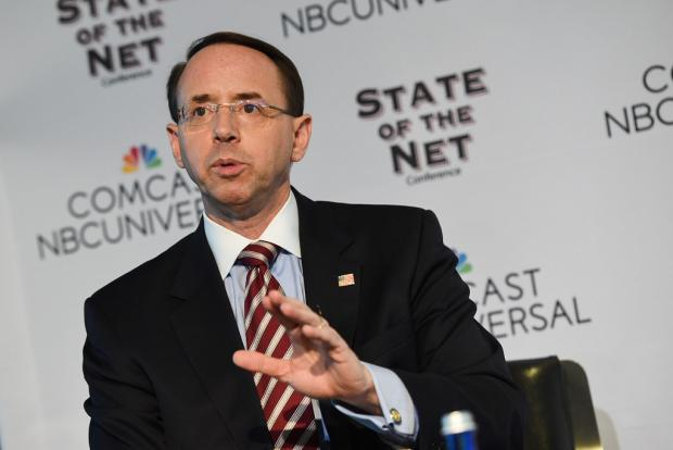 Balding white man with wire rimmed glasses wearing a suit speaking and make a hand gesture