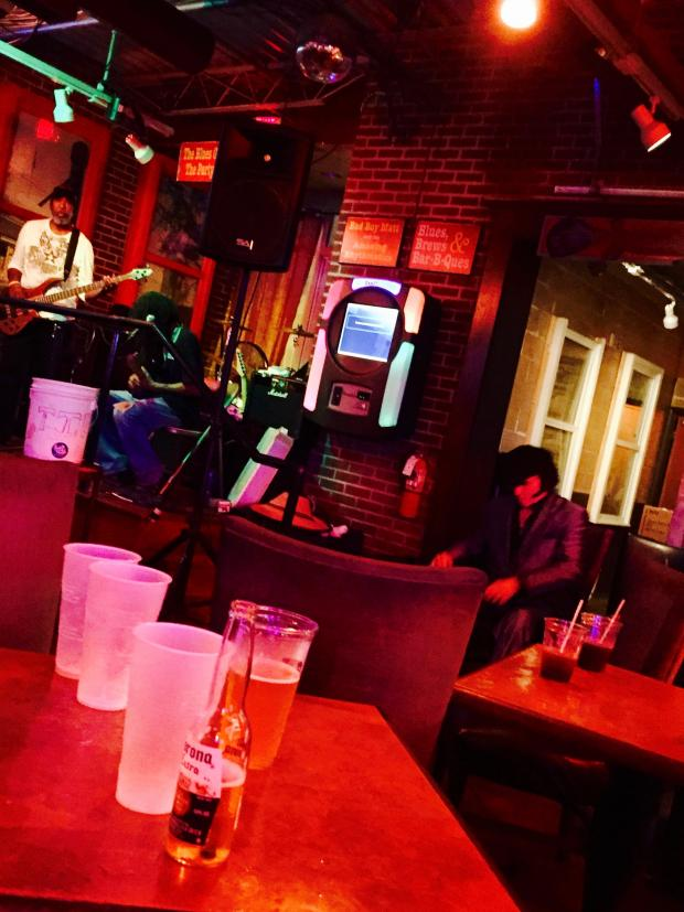 Sideways view of a bar with guy with guitar on stage lighting is very red