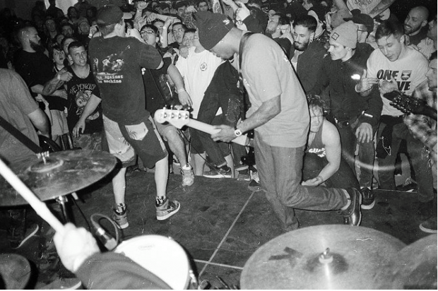 Black and white photo of black guy playing guitar with people all around dancing