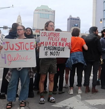 People outside downtown holding signs that say Justice 4 Julius and Columbus Police are murderers Masonique is not