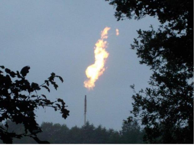 Long shot of firey emission out of smokestack
