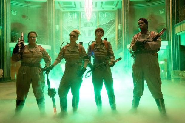 The three women in uniforms with ghost busting guns and foggy stuff around their feet