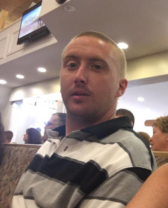 Man in his 20s with a bald head looking at the camera wearing a gray, white and black striped shirt