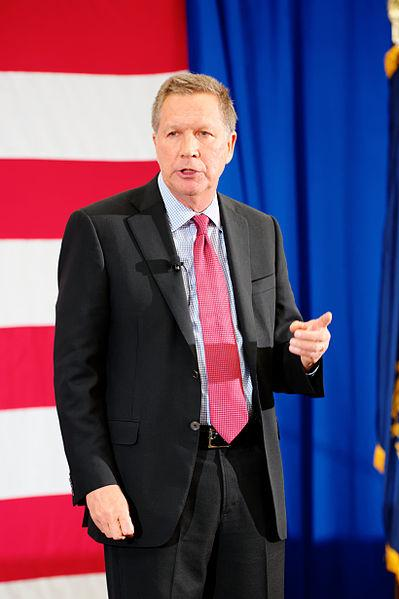 John Kasich in front of flag