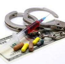 Handcuffs, a syringe, pills and a 100 dollar bill