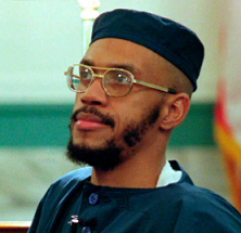 Black man with wire rimmed glasses and mustache and beard and a square topped blue hat