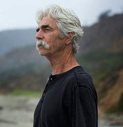 white haired man with moustache standing outside hair blowing in wind