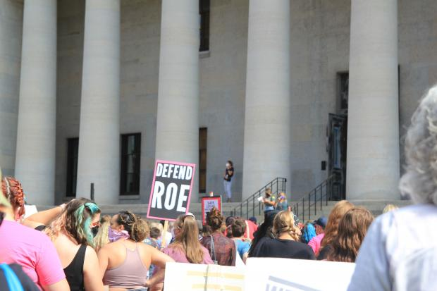 crowd protesting in front of state house with sign that says defend roe