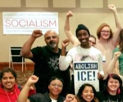 People smiling with fists in the air and a sign that says Socialism and one that says Abolish ICE