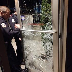 Shattered glass door and policemen