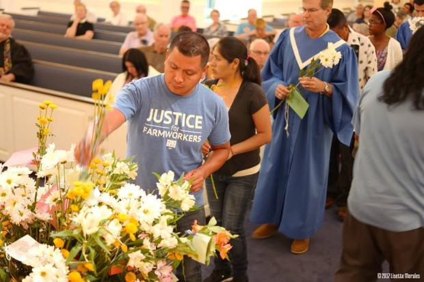 Main in a Justice for Farmworkers light blue T-shirt putting flowers into a huge container that has a lot of flowers in it and a line of people behind him and pews of a church behind them