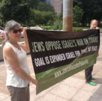 Two people holding a banner saying Jews Oppose Israel