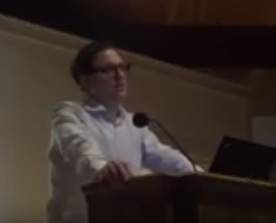 White man with glasses and white shirt standing and speaking at podium