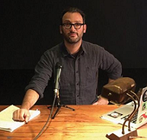 Middle aged white man with dark hair, beard and dark rimmed glasses with black shirt sitting at wooden table with a tabletop microphone in front of him and a desk lamp and a computer and papers