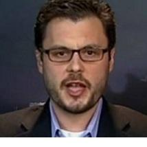 Young white man with brown-rimmed glasses with mustache and goatee talking to the camera