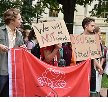 Young white people holding a big DSA sign marching