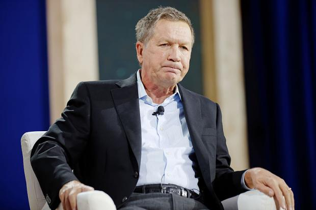 Kasich sitting and making a face
