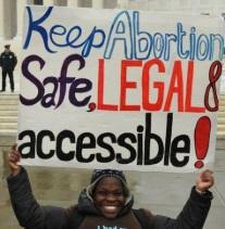 Black woman holding sign saying Keep abortion safe, legal and accessible in from of a government building with a cop standing in the background