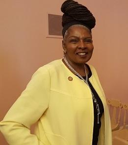 Black woman with updo wearing a yellow suit