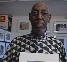 Older black man, bald with gray mustache and beard in a gray and white shirt holding a photo and standing in front of lots of other photos on the wall.