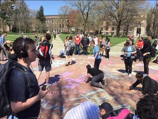 Students coloring with chalk on the Oval to cover up hate speech