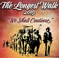 Silhouettes of native people walking with flags and the words The Longest Walk 2019 We Shall Continue