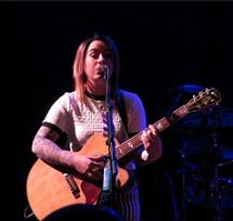 Young white woman in a white t-shirt playing a guitar and singing at a mic with a black background