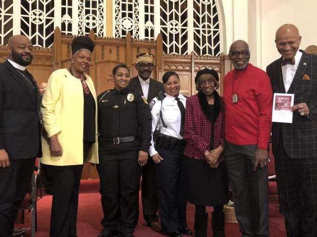 Several black men and women posing at a church