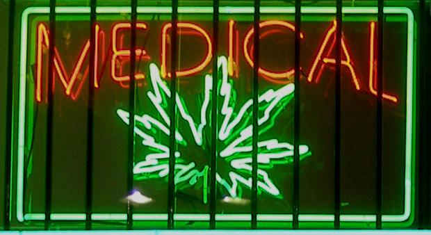 Neon sign glowing in window orange letters saying Medical and Green image of a marijuana leaf