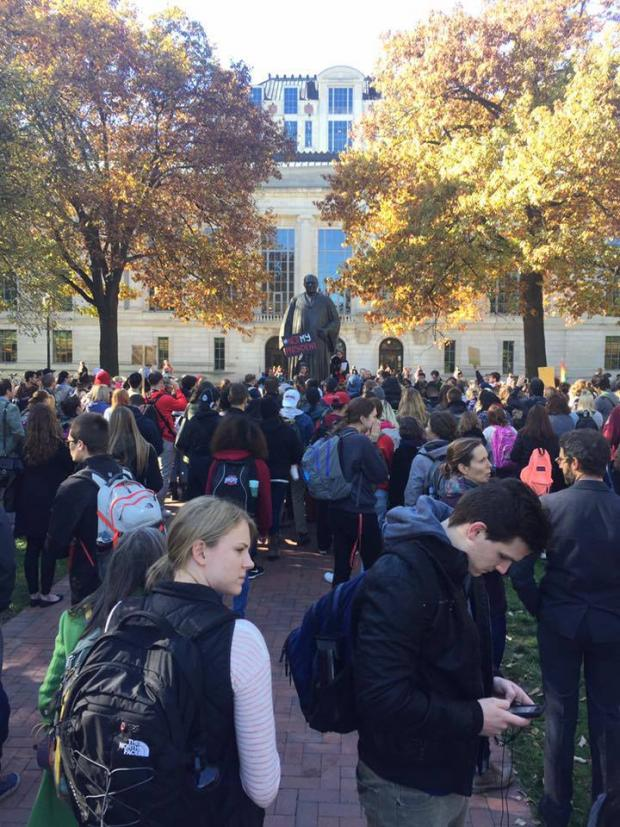 A crowd of people, mostly college students protesting around a statue with two trees on either side and a big building in the background