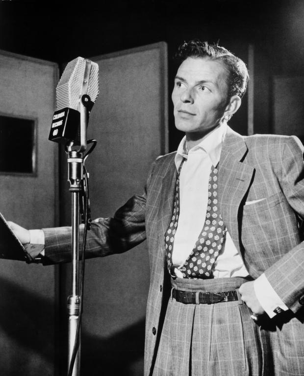 Black and white photo of young Frank Sinatra at the mic