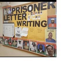 Bulletin board on the wall with words Prisoner Letter Writing and photos of a lot of men