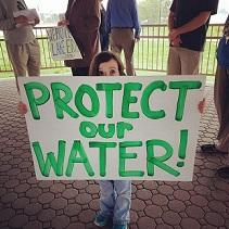Very tiny little girl holding a sign saying Protect Our Water!