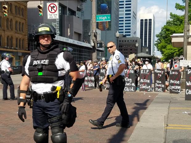 Protestors with shields as police in riot gear prepare for attack