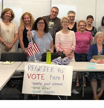 People posing standing behind a white table with a sign that says register to vote here