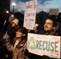People standing outside in winter coats at dusk one white man with brown hair, facial hair and glasses with a sign that reads Recuse and a white woman next to him