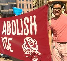 Young dark haired man with glasses holding a large red sign that says Abolish ICE with a DSA symbol of fist and rose