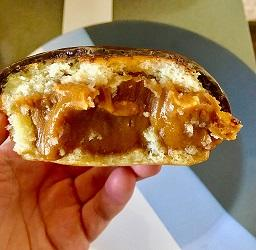 A hand holding a pastry that seems to be filled with yellowish fruit