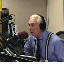 Gray haired white man in blue shirt wearing headphones talking into an elaborate microphone set up