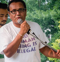 Latino man in T-shirt that says No Human Being is Illegal, talking into a mic