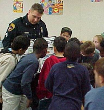 Man in police uniform surrounded by lots of small children