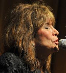 Sally Fingerett singing at a mic