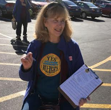 Blonde woman in blue t-shirt with a clipboard