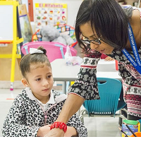 Teacher leaning over showing something to small child