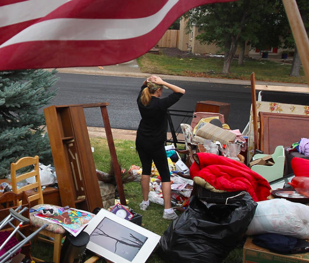 Woman outside in a yard full of furniture after eviction