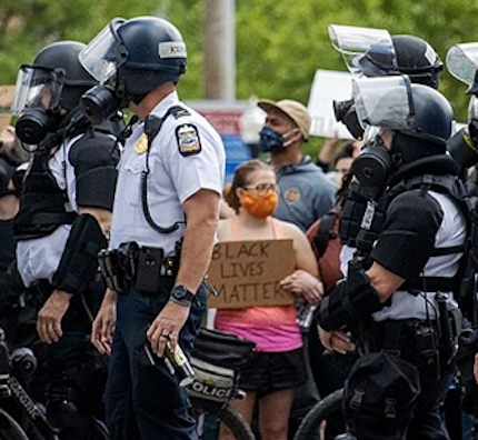 Cops and one small woman holding a BLM sign