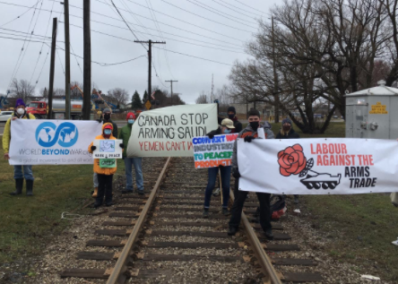 People holding signs on a railroad track
